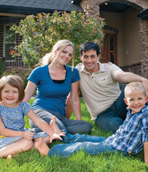 Family of four sitting on lawn
