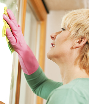 Woman wearing pink gloves cleaning window