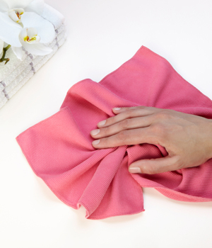 women's had cleaning counter top with pink towel