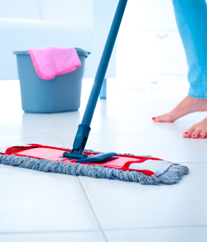 Woman mopping while tile floor barefoot
