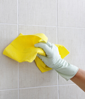 hand wearing yellow glove cleaning white tile wall