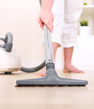Woman vacuuming floor barefoot