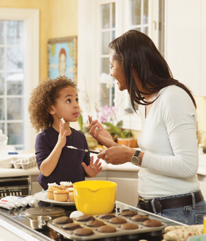 Child and mother baking cupcakes in kitchen