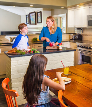 Mom and kids in kitchen preparing lunch