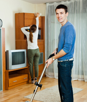 Man vacuuming and women cleaning living room