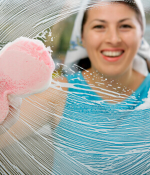 Woman cleaning window smiling
