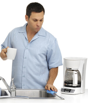 Man cleaning sink holding cup