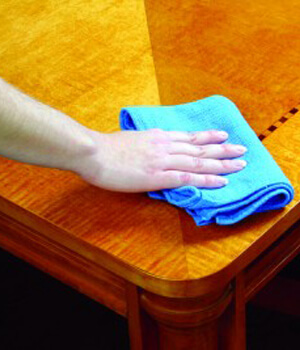 Hand cleaning wooden coffee table with blue rag