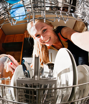 Woman smiling reaching into dishwasher