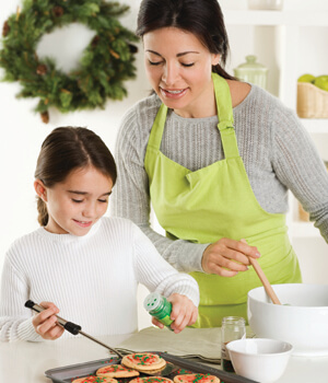 Mom and little girl baking cookies together