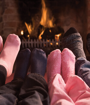 Family gathered around fireplace warming their feet