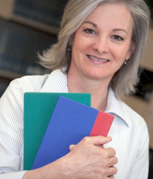 Woman smiling holding notebooks