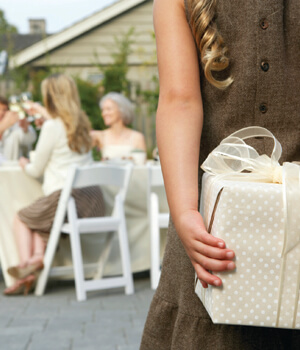 Little girl holding gift behind back at party