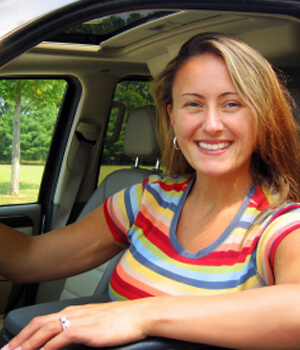 Woman in car smiling in driver seat