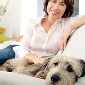 Woman sitting with dog on couch
