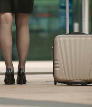 Woman dressed in business clothes traveling with luggage