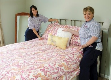 two molly maid employees making a bed