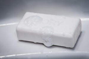 A sudsy white soap bar sitting on a bath shelf