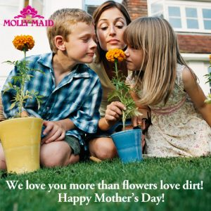 2 young children and mother in garden smelling a flower
