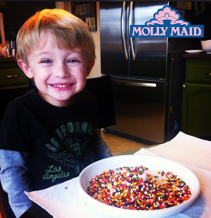young boy sitting at the kitchen counter with bowl of food smiling