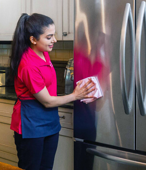 Woman cleaning outside of refrigerator